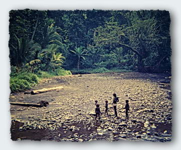Children play on edge of their jungle river.
